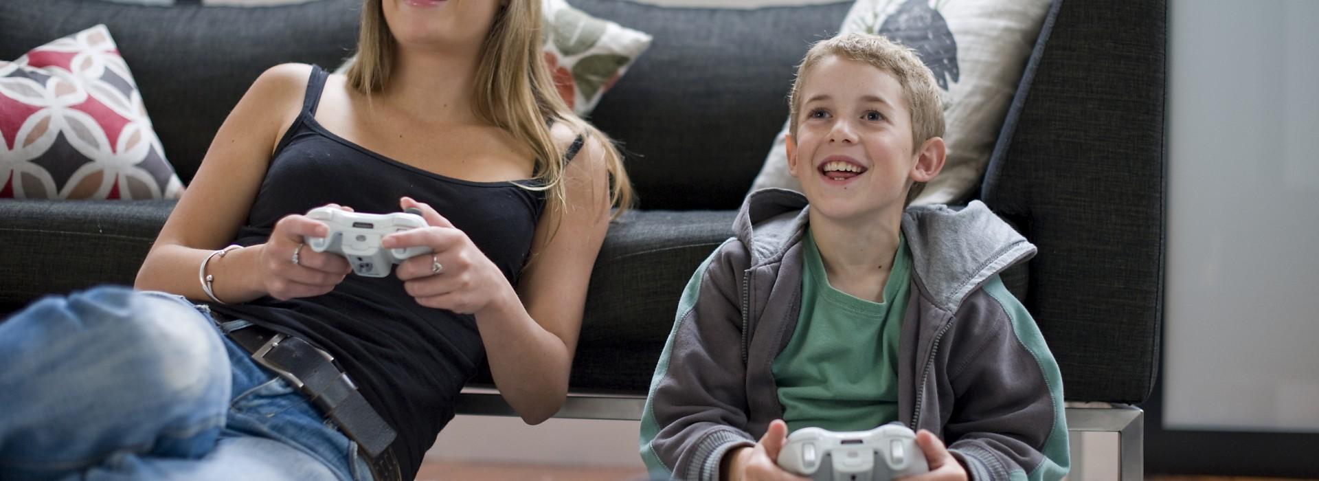 Woman (24 yrs) & boy (9 yrs) playing Xbox in apartment living room